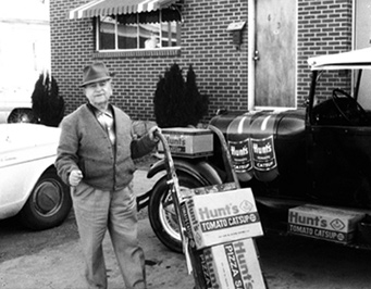 Nick W Hunt's in front of vintage vehicles